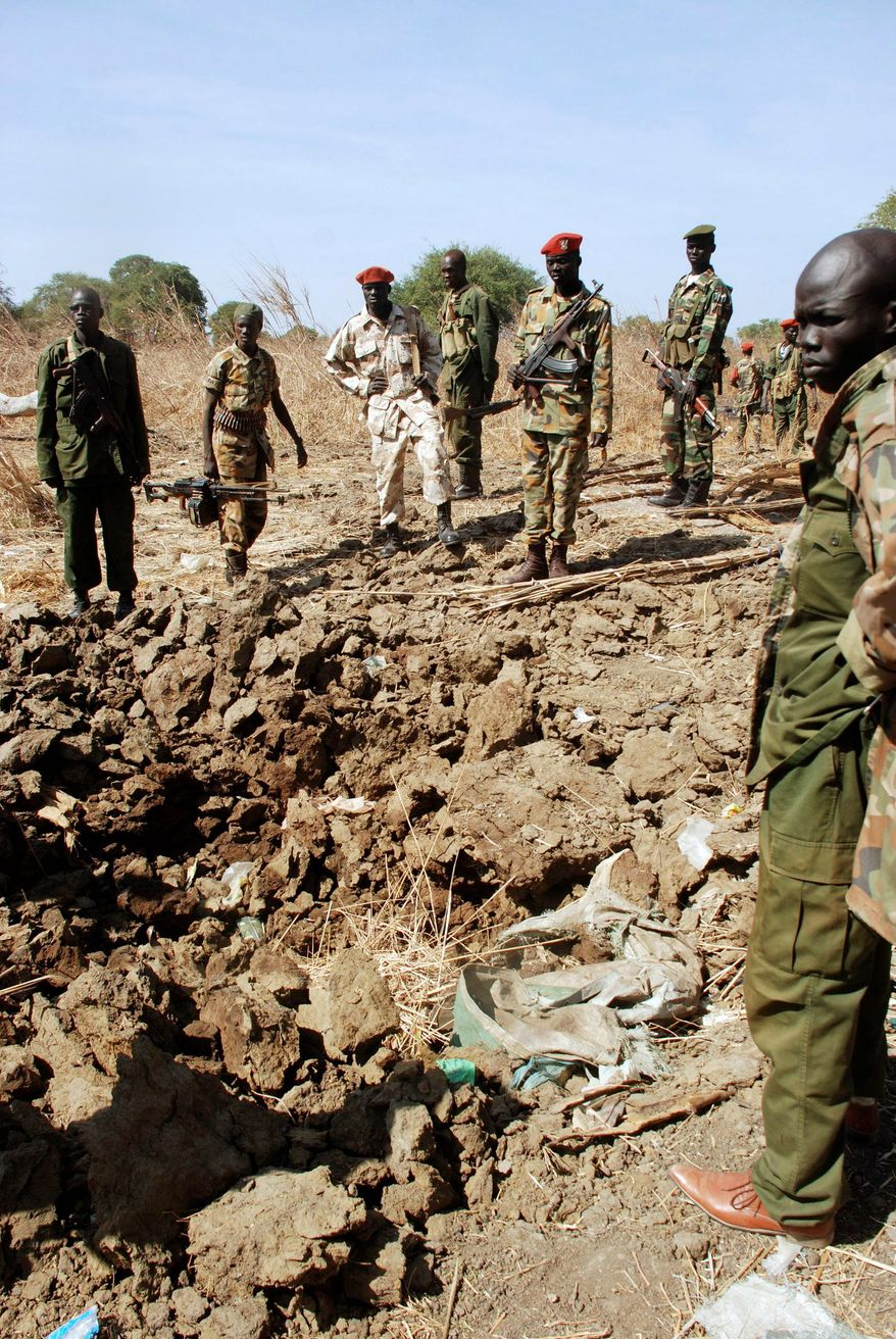 ASSOCIATED PRESS PHOTOGRAPHS Southern army officers in Northern Bahr el Ghazal state in Sudan on Saturday peer into a bomb crater created from one of the bombs dropped by the northern Sudanese army on a southern army base in the disputed border zone of Kiir Adem, where southern Sudan meets Darfur. The northern Sudanese army has launched a series of aerial bombardments in this disputed zone over the past month, and the southern army says it will not respond to these provocations in order to protect the rights of southern Sudanese to participate peacefully in their January independence referendum.