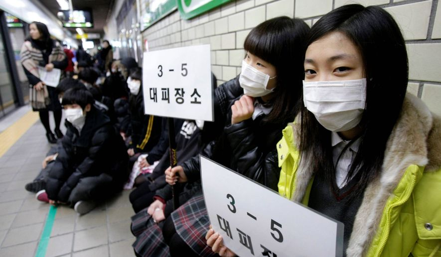 "ASSOCIATED PRESS South Korean Ahyeon Middle School students take shelter at a subway station in Seoul on Wednesday during a simulated attack by North Korea. Their signs read, ""A shelter for the 5th class of 3rd grade."""