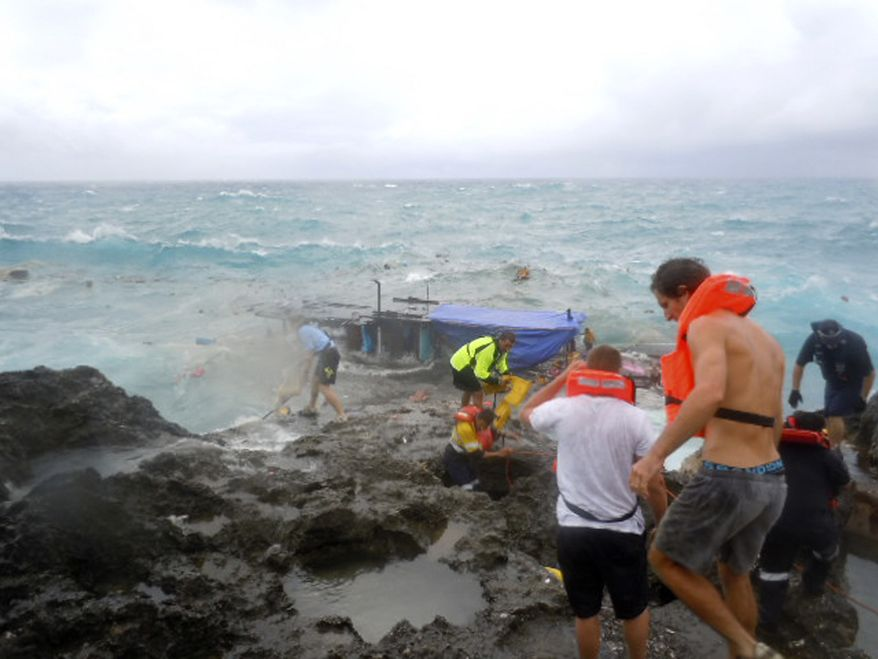 People clamber on the rocky shore of Christmas Island during a rescue attempt as a boat breaks up on Wednesday, Dec. 15, 2010. The wooden boat, packed with dozens of asylum seekers, smashed apart on cliff-side rocks in heavy seas off the Australian island, sending some to their deaths in the churning whitewater. (AP Photo/ABC)
