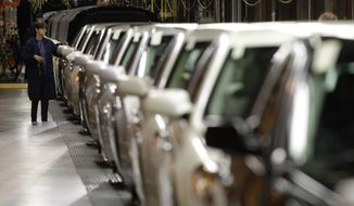 A line worker checks vehicles at the General Motors Hamtramck assembly plant in Hamtramck, Mich., Tuesday, Nov. 30, 2010. U.S. factory output grew for the 16th straight month in November, though at a slightly slower pace than the previous month.(AP Photo/Paul Sancya) **FILE**