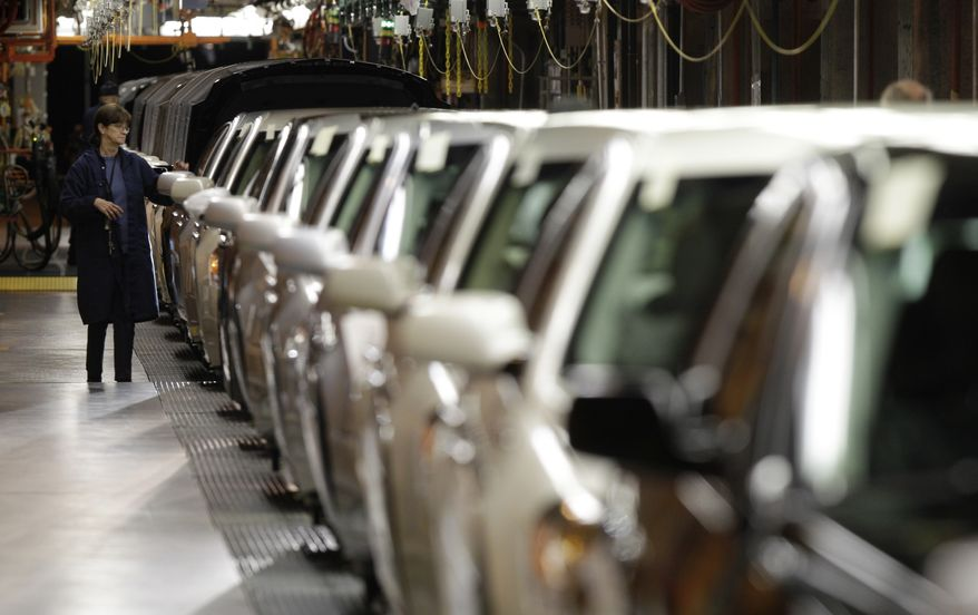 A line worker checks vehicles at the General Motors Hamtramck assembly plant in Hamtramck, Mich., Tuesday, Nov. 30, 2010. U.S. factory output grew for the 16th straight month in November, though at a slightly slower pace than the previous month.(AP Photo/Paul Sancya)