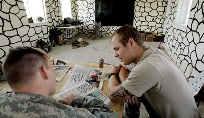 ASSOCIATED PRESS PHOTOGRAPHS Staff Sgt. Brandon Griffis (right) of Pendleton, Ind., whiled away the time earlier this year inside the Pir Mohammed school in Kandahar province. The school was turned into a de facto military base, which upset village elders.