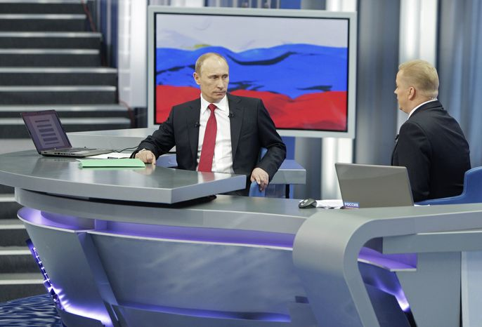 Russian Prime Minister Vladimir Putin (left) listens to a question during a call-in session broadcast live on Russian state television and radio from Moscow on Thursday, Dec. 16, 2010. (AP Photo/RIA Novosti, Alexei Druzhinin, Pool)