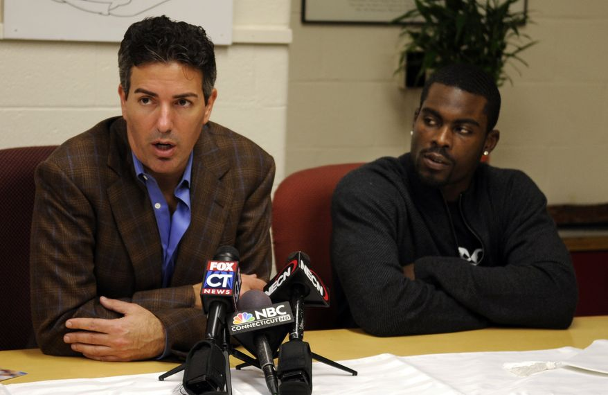 Wayne Pacelle, president and CEO of the Humane Society of the United States, left, speaks at a press conferece after Philadelphia Eagles quarterback Michael Vick, right, spoke to students at Wilbur Cross High School in New Haven, Conn., Tuesday, Nov. 23, 2010. Vick urged high school students in Connecticut to show kindness toward animals, adding to the string of appearances he's made since returning from a dogfighting conviction to become one of the NFL's most exciting players. (AP Photo/Bob Child)