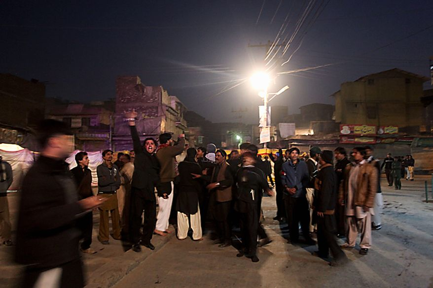 Shi'ite Muslims chant anti-government slogans at the site of an explosion in Peshawar, Pakistan, on Thursday, Dec. 16, 2010. An assailant threw an explosive device at Shi'ite Muslims carrying out a Muharram procession in the city, wounding several people. (AP Photo/Mohammad Sajjad)