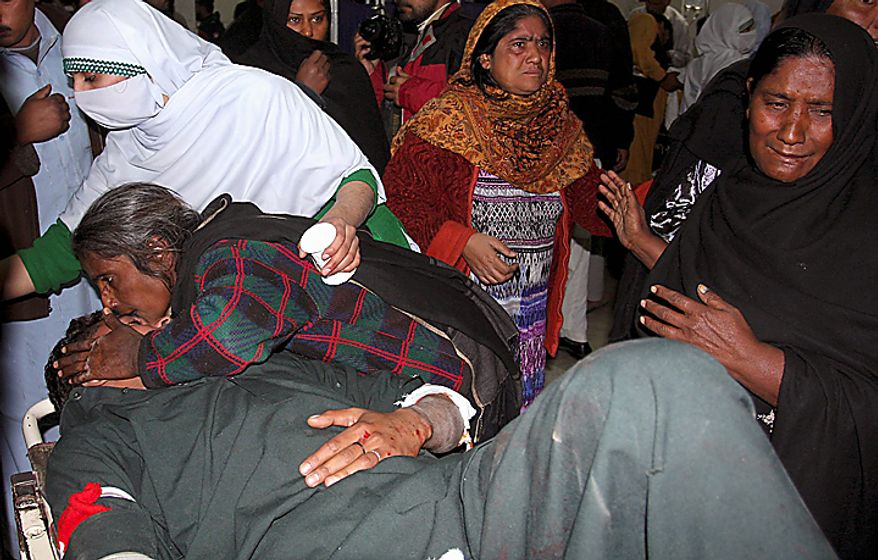 A woman kisses her injured son at a local hospital in Peshawar, Pakistan, on Thursday, Dec. 16, 2010, after an assailant threw an explosive device at Shi'ite Muslims in a Muharram procession in the city, wounding several people. (AP Photo/Mohammad Sajjad)