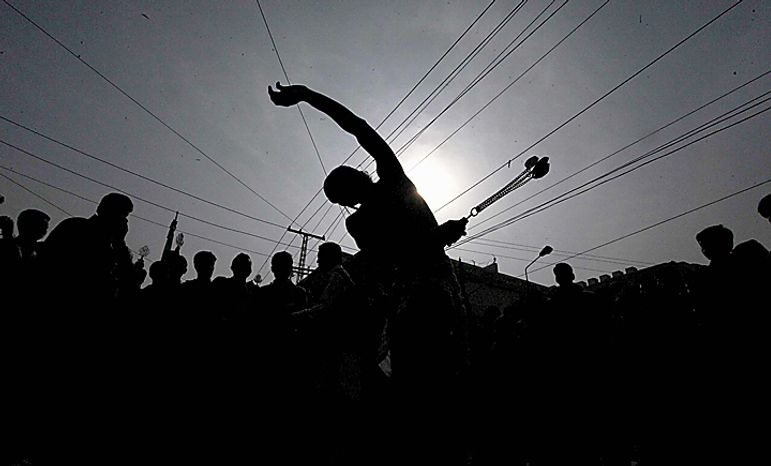 A Shi'ite Muslim flagelates himself with knives during a Muharram procession in Peshawar, Pakistan, Thursday, Dec. 16, 2010. Muharram is observed around the world for ten days as mourning in remembrance of the martyrdom of Imam Hussein, the grandson of Prophet Muhammad. (AP Photo/Mohammad Sajjad)