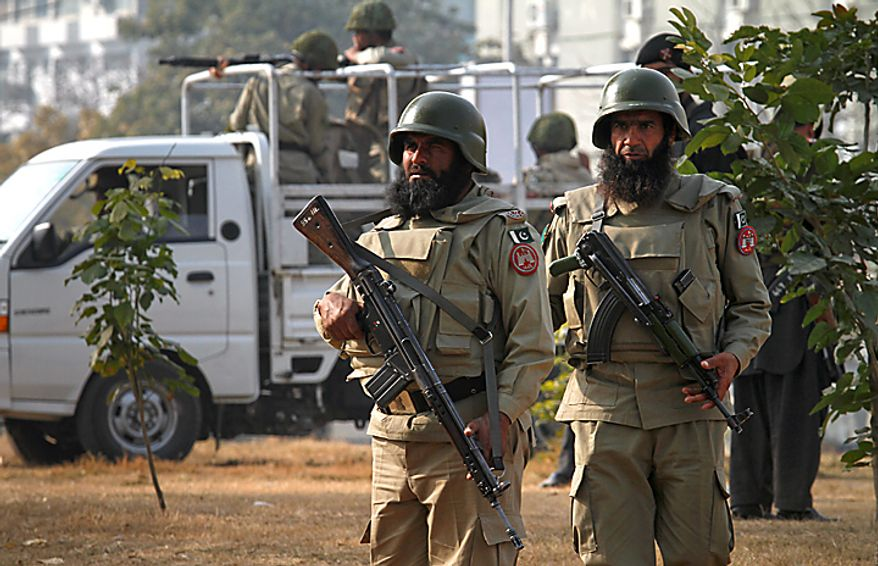 Paramilitary soldiers stand guard near the the Muharram procession in Islamabad, Pakistan, on Thursday, Dec. 16, 2010. Muharram is observed around the world for ten days as mourning in remembrance of the martyrdom of Imam Hussein, the grandson of Prophet Muhammad. (AP Photo/Anjum Naveed)
