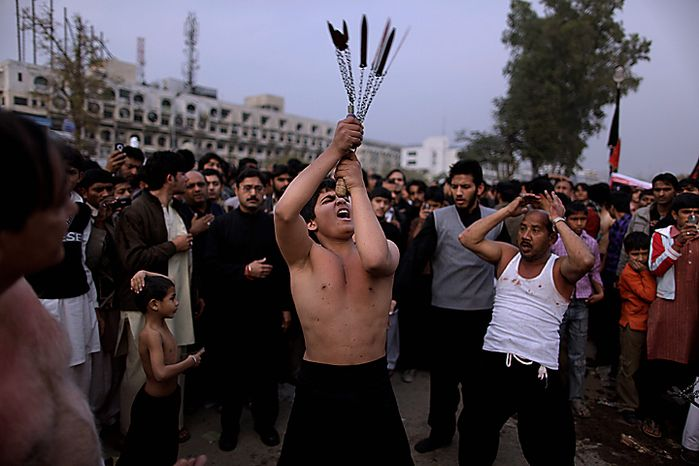 A Shi'ite youth beats himself with knives during the Muharram procession in Islamabad, Pakistan, Thursday, Dec. 16, 2010. Muharram is observed around the world for ten days as mourning in remembrance of the martyrdom of Imam Hussein, the grandson of Prophet Muhammad. (AP Photo/Muhammed Muheisen)