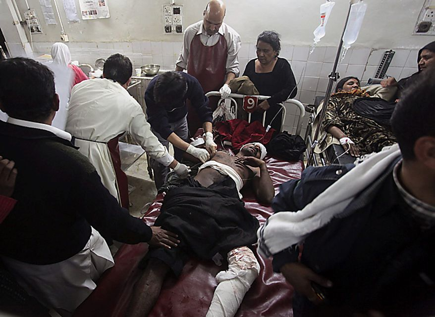 An injured victim is treated at a local hospital in Peshawar, Pakistan, on Thursday, Dec. 16, 2010, after an assailant threw an explosive device at Shi'ite Muslims in a Muharram procession in the city, wounding several people. (AP Photo/Mohammad Sajjad)