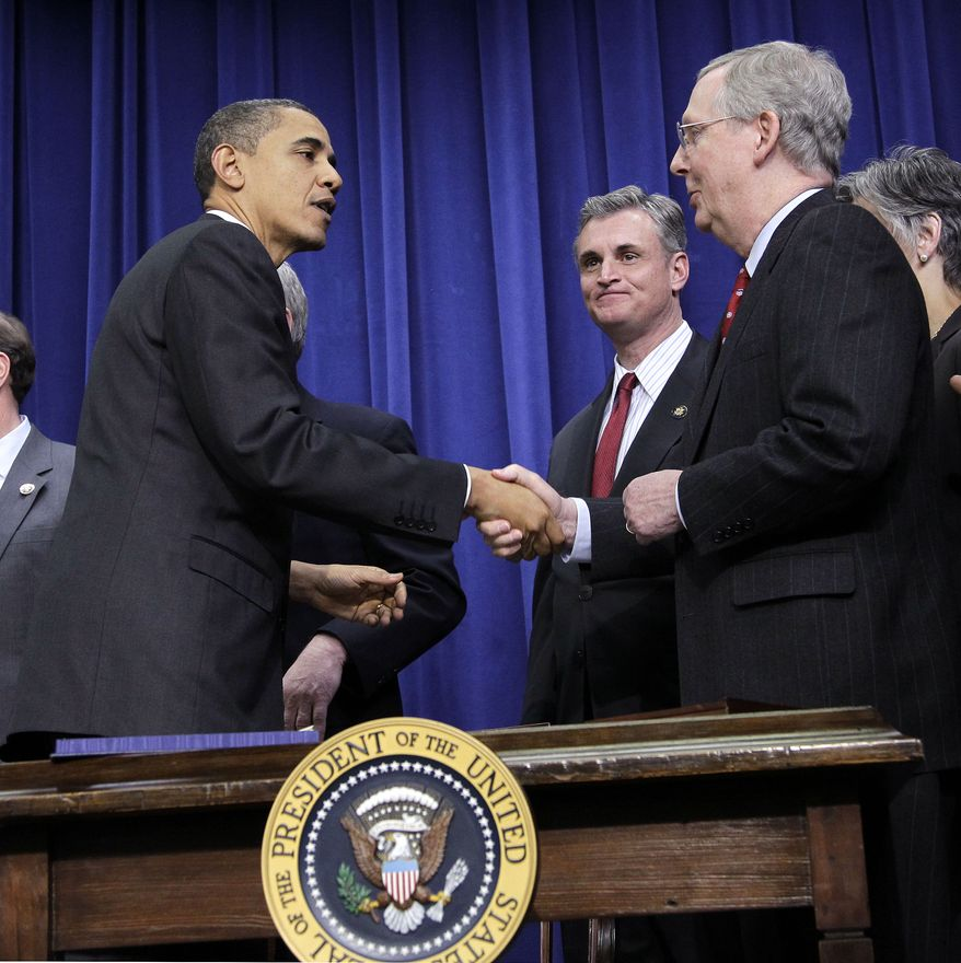 President Obama, left, shakes hands with Senate Republican Leader Mitch McConnell of Kentucky, right, after signing the $858 billion tax deal into law in a ceremony in the Eisenhower Executive Office Building on the White House complex, Friday, Dec. 17, 2010 in Washington. (AP Photo/Pablo Martinez Monsivais)