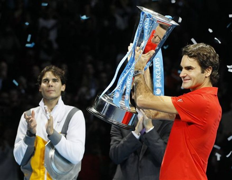 FOR SPANISH END OF THE YEAR STORY 2010 TENNIS - FILE - In this Nov. 28, 2010 file photo Switzerland's Roger Federer celebrates as he holds the trophy after beating Spain's Rafael Nadal, left,  to win the singles final tennis match at the ATP World Tour Finals at the O2 Arena in London.  (AP Photo/Kirsty Wigglesworth, File)