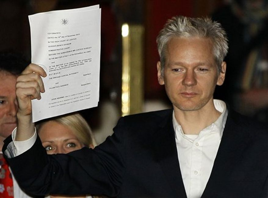 WikiLeaks founder Julian Assange holds up a court document for the media outside the High Court in London on Thursday, Dec. 16, 2010, after he was released on bail. (AP Photo/Kirsty Wigglesworth)