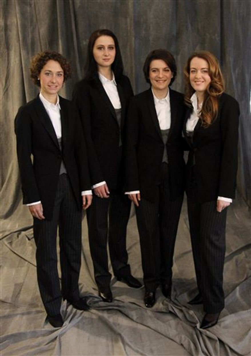 Charlotte Balzereit, harp, designer Markus Binder, Olesya Kurylyak, first violin,  Albena Danailova, concert master, and Isabelle Ballot, first violin, from left, of the the Vienna Philharmonic Orchestra pose for a photo in their new ladies clothing at the traditional New Year's concert at Vienna's Musikverein in Vienna, Austria, on Wednesday, Dec. 15, 2010. The female musicians will first wear their new attire at the Vienna Philharmonic's traditional New Year's concert. (AP Photo/Ronald Zak)