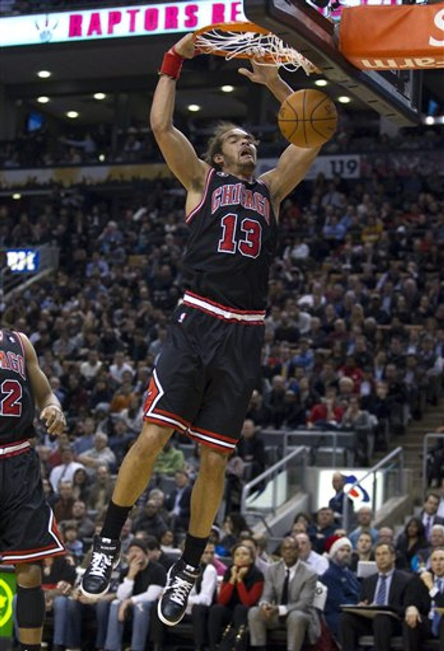 Chicago Bulls forward Carlos Boozer (5) drives to the hoop against Toronto Raptors forward Amir Johnson (15) during first half NBA basketball action in Toronto on Wednesday, Dec. 15, 2010. (AP Photo/The Canadian Press, Frank Gunn)