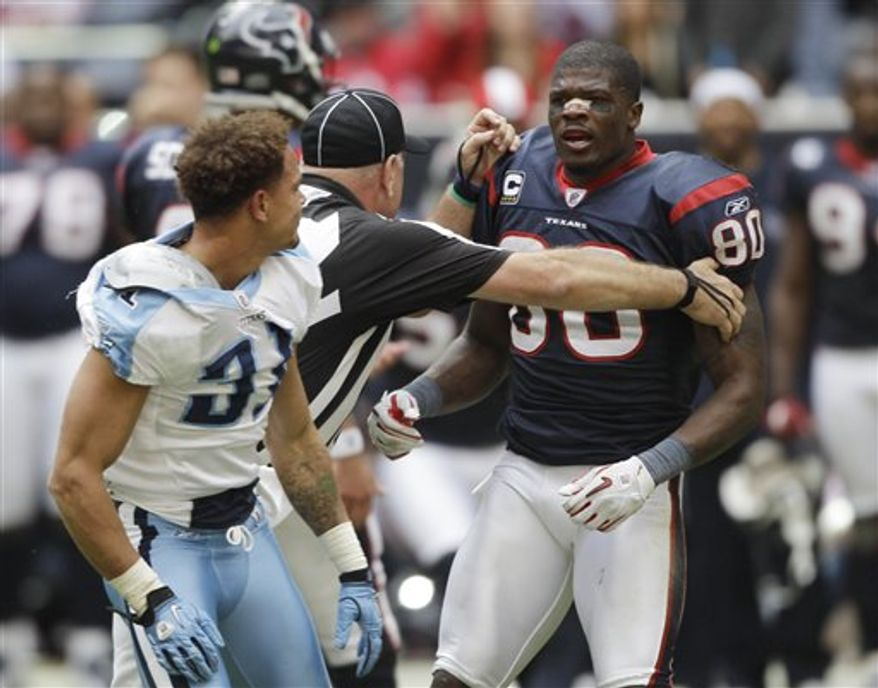 FILE - This Nov. 28, 2010, file photo shows an official stepping between Tennessee Titans cornerback Cortland Finnegan (31) and Houston Texans wide receiver Andre Johnson (80) in the fourth quarter of an NFL football game, in Houston. Titans coach Jeff Fisher plans to keep Finnegan defending Texans' Johnson throughout Sunday's, Dec. 19, game, even though the last time Fisher did that Johnson yanked Finnegan's helmet off and punched him three times.(AP Photo/David J. Phillip, File)