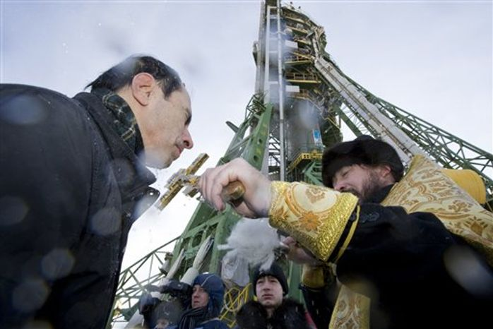 A Russian Orthodox priest blesses the Soyuz TMA-20 spacecraft at the launch pad at the Baikonur Cosmodrome on Tuesday, Dec. 14, 2010. The crew of NASA astronaut Catherine Coleman, Russian cosmonaut Dmitry Kondratyev and European Space Agency Astronaut Paolo Nespoli are to travel to the International Space Station on Dec. 16, 2010. (AP photo/Shamil Zhumatov, pool)