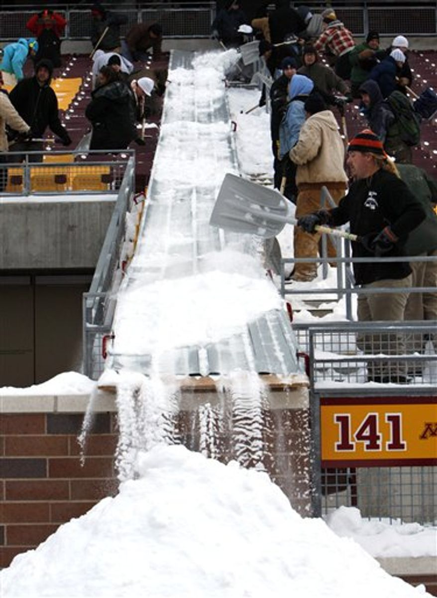 Workers are shown beneath the snow-damaged roof inside the Metrodome in Minneapolis, Friday, Dec. 17, 2010.  (AP Photo/The Star Tribune, Elizabeth Flores)
