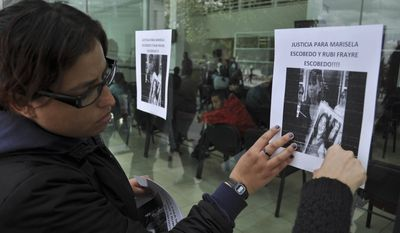 Human rights activists hang a sign on the wall of the state prosecutors office to protest the killing of Marisela Escobedo Ortiz in Ciudad Juarez, Mexico, Friday Dec. 17, 2010. Ms. Escobedo Ortiz, who had been protesting for three days in front of the governor's office in Chihuahua city to demand justice for her slain daughter, was shot in the head Thursday by unknown assailants in front of the governor's office. (AP Photo/Raymundo Ruiz)