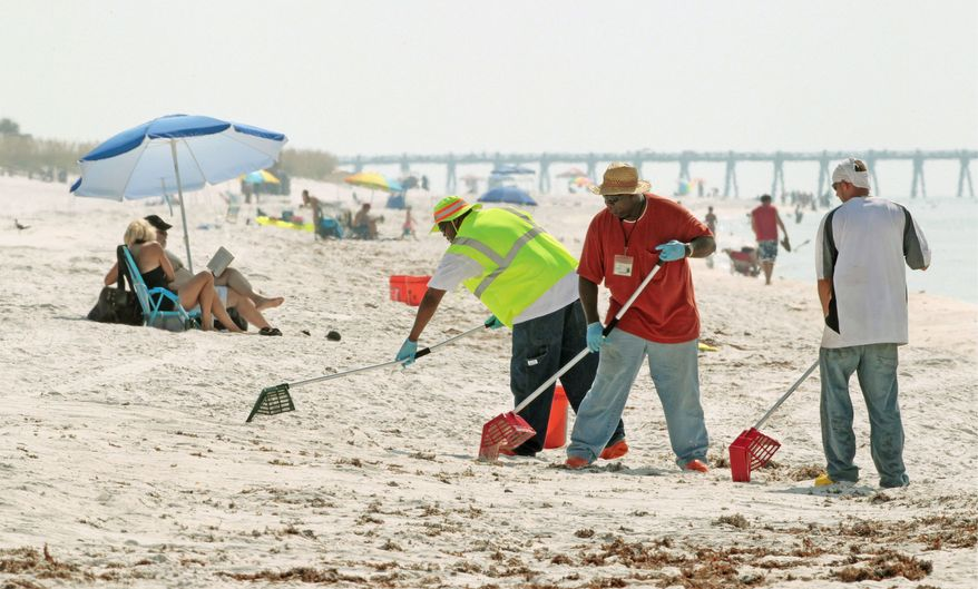 Workers clean up tar balls on Pensacola Beach, Fla. The lingering economic recession, a record cold Florida winter and the effects of the Gulf oil spill stalled the tourist traffic this year in parts of Florida.