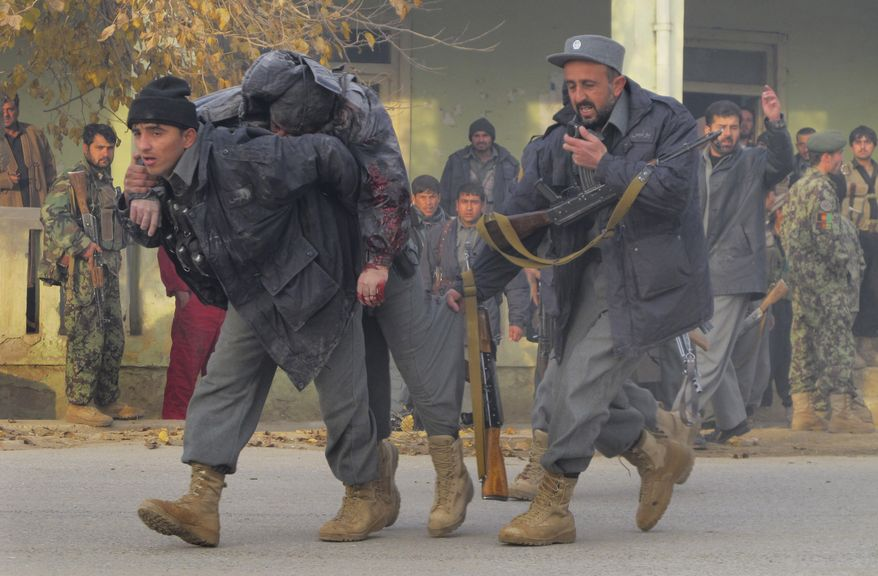 Afghan policemen carry away a wounded colleague during a gunbattle in Kunduz, north of Kabul, Afghanistan, on Sunday, Dec. 19, 2010. Teams of Taliban militants assaulted the Afghan army in the north of the country and in the capital, killing at least 13 members of the security forces, officials said. (AP Photo/Fulad Hamdard)
