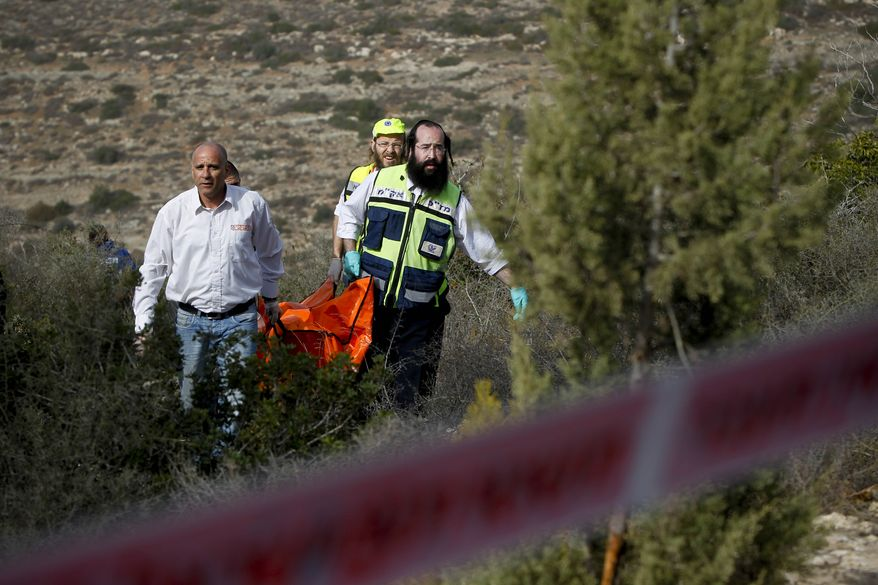 Israeli rescue workers carry the body of U.S. tourist Kristine Luken after she was found in a wooded area near the village of Mata, outside Jerusalem, on Sunday, Dec. 19, 2010. Israeli police originally identified her as Christine Logan. (AP Photo/Tara Todras-Whitehill)