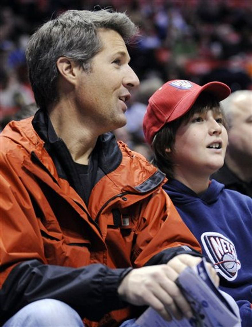 """FILE - In this Jan. 15, 2010 file photo, David Goldman, left, and his son Sean watch the New Jersey Nets play the Indiana Pacers in an NBA basketball game in East Rutherford, N.J. Goldman was reunited with his son last December after a bitter five-year battle in Brazil to regain custody. Goldman has written a book, """"A Father's Love,"""" that will be released in May 2011.  (AP Photo/Bill Kostroun, file)"""