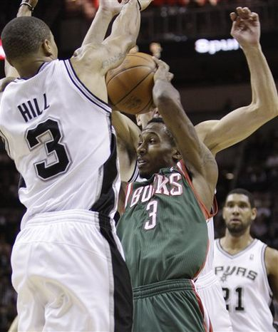 Milwaukee Bucks' Brandon Jennings (3) is defended by San Antonio Spurs' George Hill (3) and Matt Bonner during the fourth quarter of an NBA basketball game, Wednesday, Dec. 15, 2010 in San Antonio. San Antonio won 92-90. (AP Photo/Eric Gay)