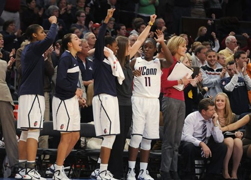 Connecticut's Maya Moore, right, and coach Geno Auriemma celebrate in the second half of the second NCAA college basketball game of the Maggie Dixon Classic at Madison Square Garden in New York, Sunday, Dec. 19, 2010. Connecticut won their 88th game in a row, 81-50.  (AP Photo/Henny Ray Abrams)