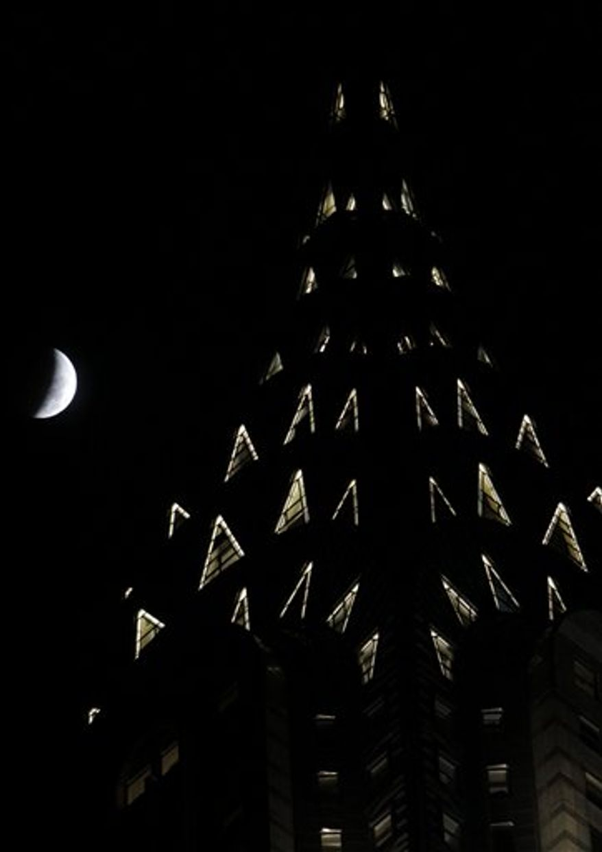 A series of photos taken over an hour long period show the full moon as it is shadowed by the Earth as a total lunar eclipse marks the arrival of the winter solstice Tuesday, December 21, 2010 in Overland Park, Kan. (AP Photo/Charlie Riedel)