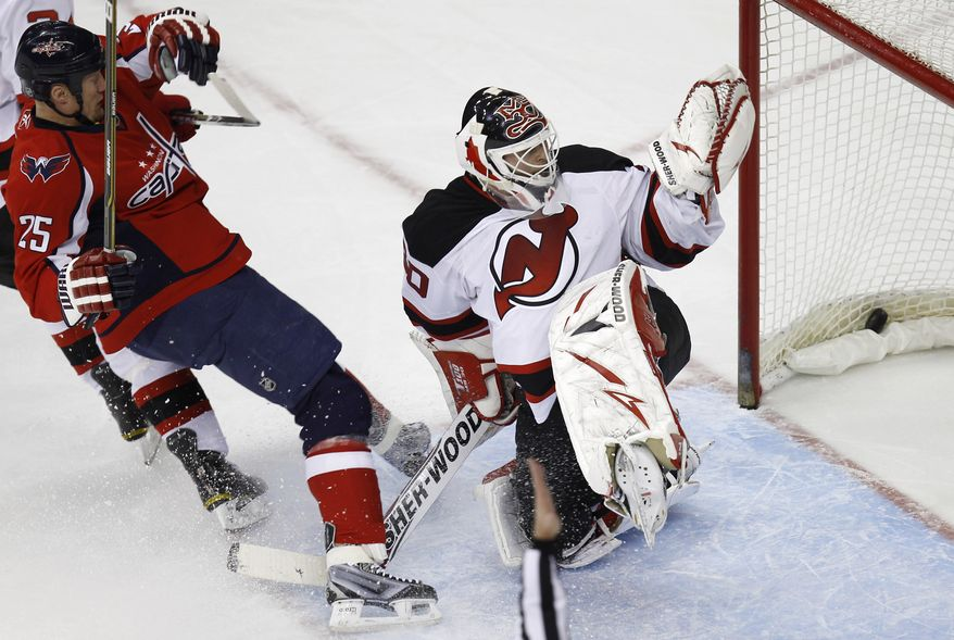 Washington Capitals' Jason Chimera (25) falls after scoring a goal aginst New Jersey Devils goalie Martin Brodeur during the second period of an NHL hockey game Tuesday, Dec. 21, 2010, in Washington. (AP Photo/Luis M. Alvarez)