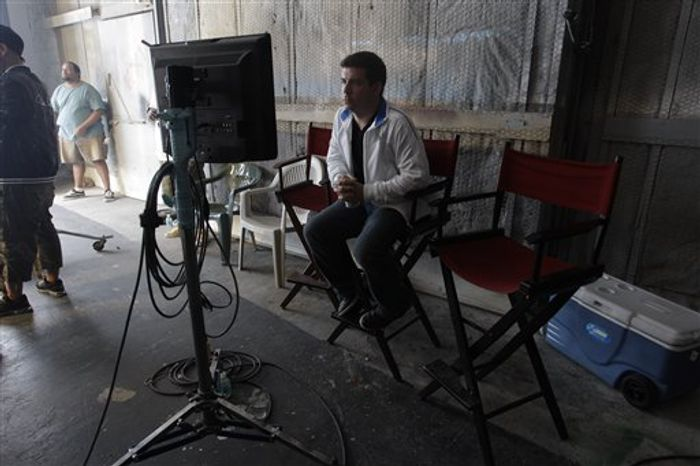 In this Oct. 10, 2010 photo, David Rousseau, stands in a Miami sound stage as Pit Bull records a music video.  As a child, music video director  Rousseau lived in Miami's Little Havana neighborhood and would listen to the songs wafting from the nearby Orange Bowl. It was the 1980s and all the biggest acts played there: Pink Floyd, Genesis, Bruce Springsteen and Michael Jackson. It made him envision what the music would look like. Today, Rousseau, 35, has directed videos for some of music's biggest acts: Lil Wayne, Enrique Iglesias, Pitbull, and T-Pain. He is known for bright colors and graphics that complement the high-energy music he's showcasing.  (AP Photo/J Pat Carter)