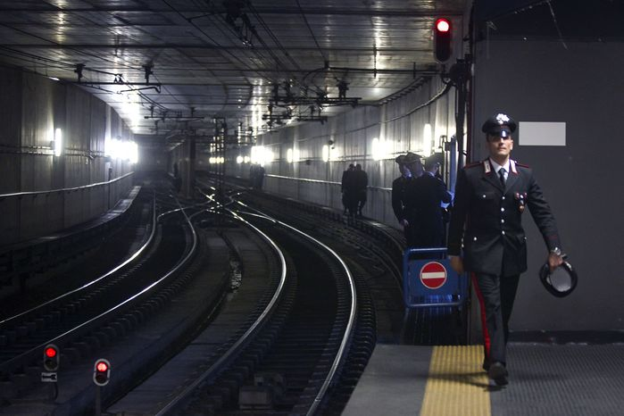 Italian police patrol the access to the rails at the Rebibbia subway station in Rome after a bomb scare on Tuesday, Dec. 21, 2010. A suspicious package full of wires and powder was found in a subway car, prompting a terror scare during the Christmas season. Bomb-disposal experts checked the powder and concluded that the device could not have exploded. (AP Photo/Angelo Carconi)