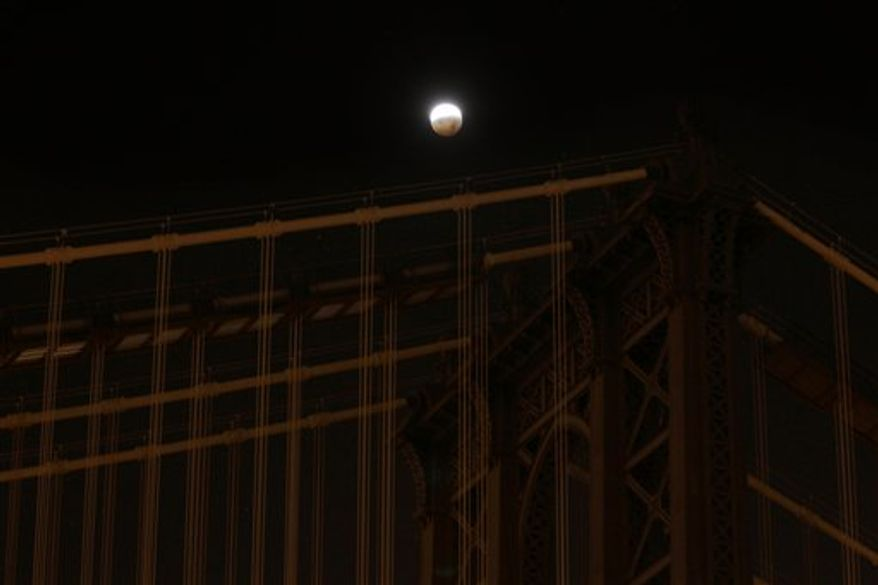 The moon is seen through supports for the Verrazano-Narrows Bridge between the Brooklyn and Staten Island boroughs of New York, during the lunar eclipse early Tuesday, Dec. 21, 2010. (AP Photo/David Boe)