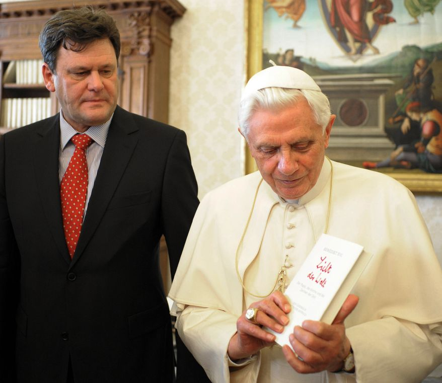 "Pope Benedict XVI holds a copy of the book ""Light of the World,'' a series of papal interviews with German journalist Peter Seewald (left), at the Vatican on Tuesday, Nov. 23, 2010. (AP Photo/L'Osservatore Romano, HO)"