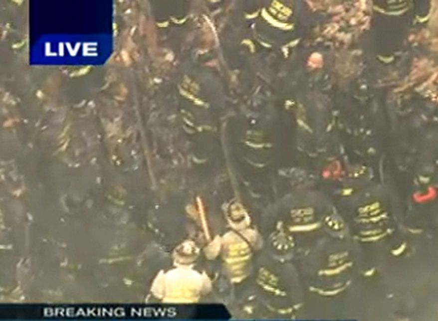 In this frame grab made from WGN-TV, Chicago firefighters work to save firefighters that were trapped when a wall collapsed on Wednesday Dec. 22, 2010, in Chicago's South Side while they were fighting a blaze at an abandoned commercial building. Fire Media Affairs Director Larry Langford confirmed that firefighters were unaccounted for at the scene on Chicago's South Side and that rescue crews were working to save them. (AP Photo/Courtesy WGN-TV)