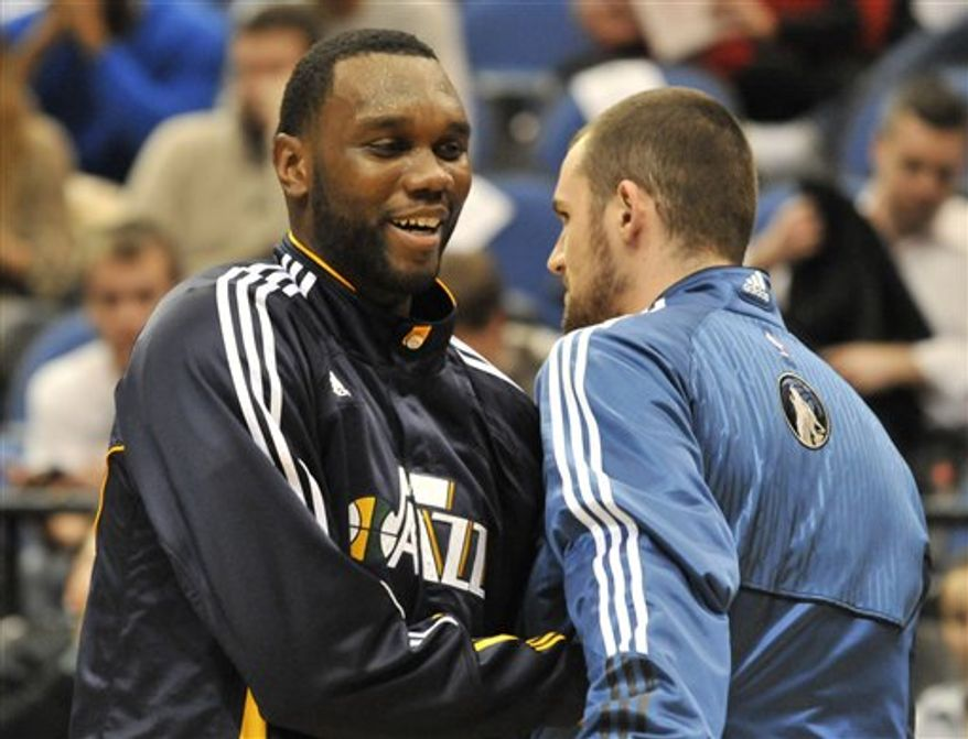 Utah Jazz's Al Jefferson is fouled by Minnesota Timberwolves' Kevin Love in the first half of an NBA basketball game Wednesday, Dec. 22, 2010 in Minneapolis. (AP Photo/Jim Mone)