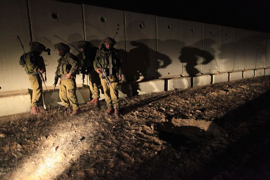 ** FILE ** Israeli soldiers in southern Israel near the Israel-Gaza border examine a crater created by a rocket fired by Palestinian militants from the Gaza Strip on Thursday, Dec. 9, 2010. (AP Photo/Tsafrir Abayov)
