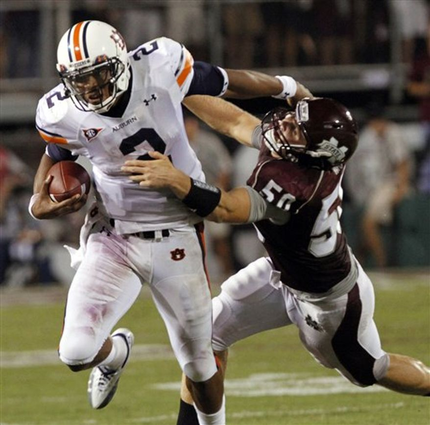 FILE - In this Sept. 9, 2010, file photo, Auburn quarterback Cameron Newton (2) struggles to ward off a third-quarter tackle by Mississippi State linebacker Chris White (50) in an NCAA college football game in Starkville, Miss. Although Auburn won, 17-14 and the defense almost shut down Auburn's Heisman winning quarterback, White and the rest of the Mississippi State defenders will have to contend with the dynamic Michigan quarterback Denard Robinson when the two squads meet at the Gator Bowl, Jan. 1 2011. (AP Photo/Rogelio V. Solis, File)