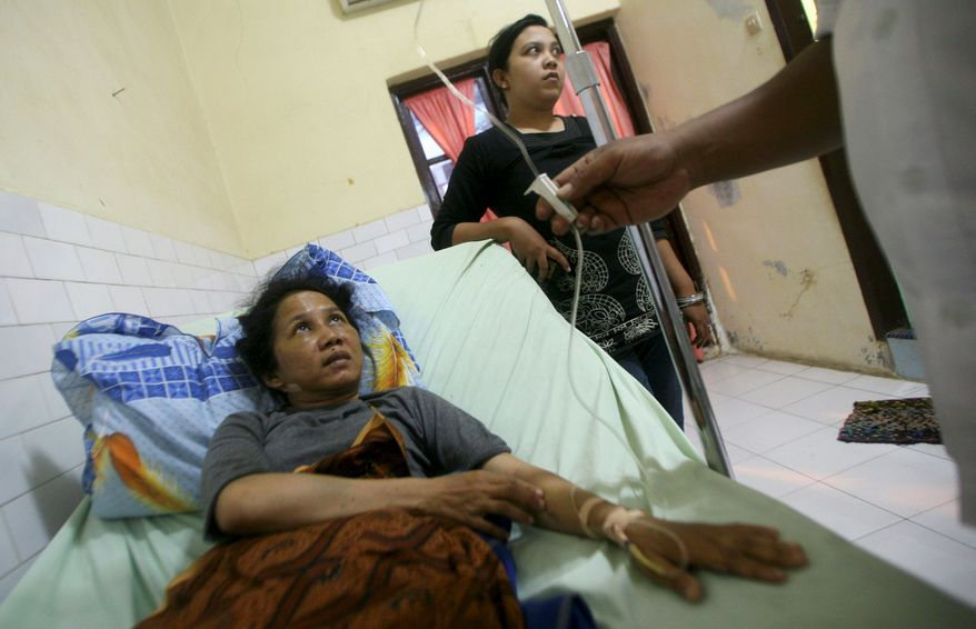 Titik Yuniarti is treated Dec. 15 in a Langsa, Indonesia, hospital for her injuries after she was beaten by a mob accusing her of attempting to abduct a child while searching for her daughter, who went missing in the 2004 Indian Ocean tsunami.