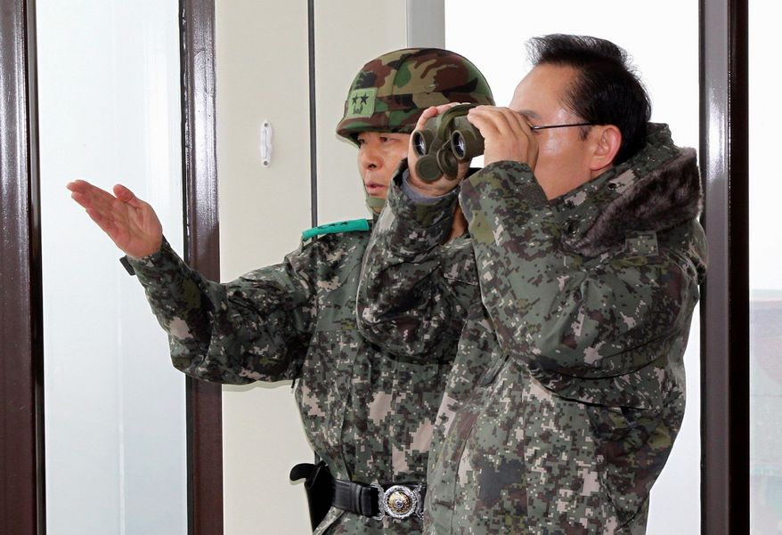 ASSOCIATED PRESS South Korean President Lee Myung-bak looks at North Korea through binoculars Thursday from Yanggu, north of Seoul, as his army and air force staged their largest firing drills of the year.
