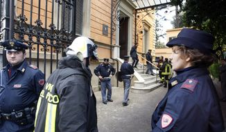 Police officers and a firefighter stand outside the Chilean Embassy in Rome on Thursday, Dec. 23, 2010, after a pair of package bombs exploded at the Swiss and Chilean embassies, injuring the two people who opened them, officials said. Police ordered checks at all embassies after a false alarm also was reported at the Ukrainian Embassy. (AP Photo/Andrew Medichini)