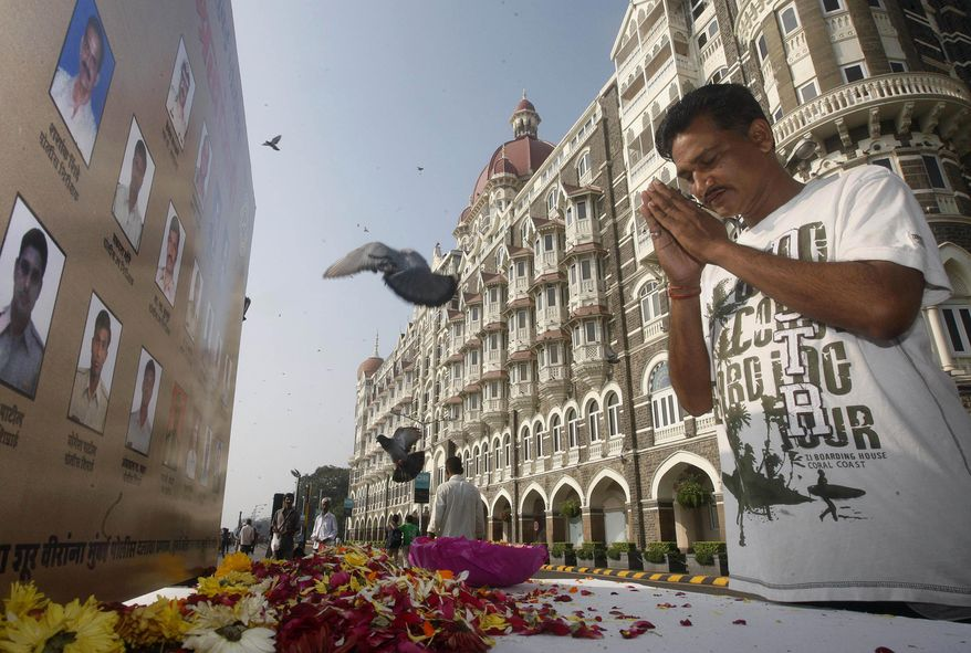 ** FILE ** A man pays homage in front of portraits of police officers killed in the Mumbai terror attack outside the Taj Mahal Palace hotel, one of the sites of the attack, on the second anniversary of the attack in Mumbai, India, on Friday, Nov. 26, 2010. (AP Photo/Rafiq Maqbool)