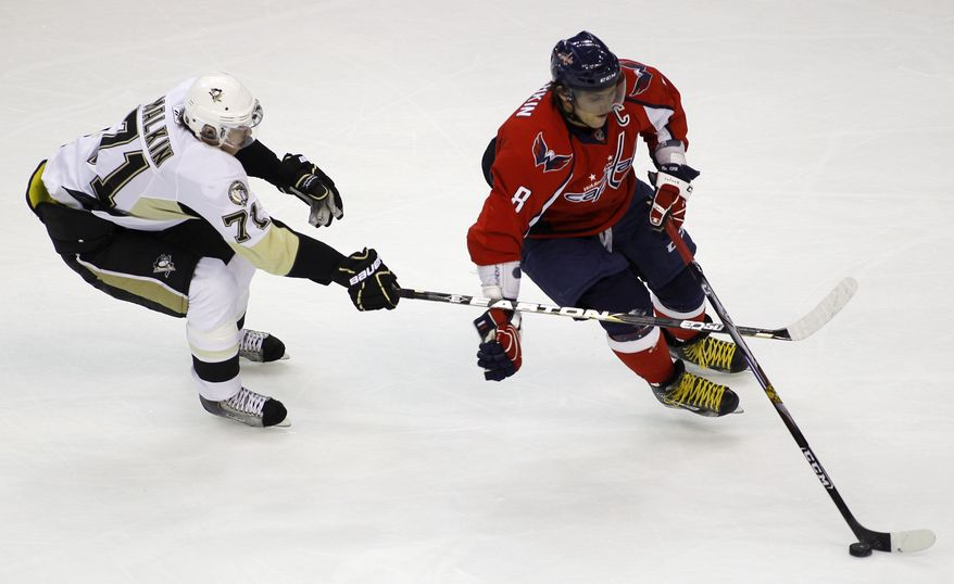 Washington Capitals' Alex Ovechkin (8), of Russia, moves the puck as Pittsburgh Penguins' Evgeni Malkin (71), of Russia, defends during the first period of an NHL hockey game Thursday, Dec. 23, 2010, in Washington. The Penguins won 3-2 in a shootout. (AP Photo/Luis M. Alvarez)