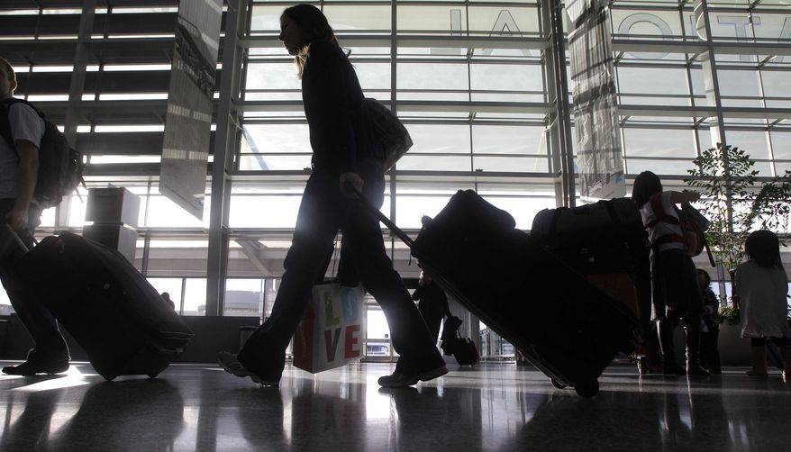 ** FILE ** A woman pulls her travel bag in the International terminal at San Francisco International Airport in San Francisco on Thursday, Dec. 23, 2010. (AP Photo/Jeff Chiu