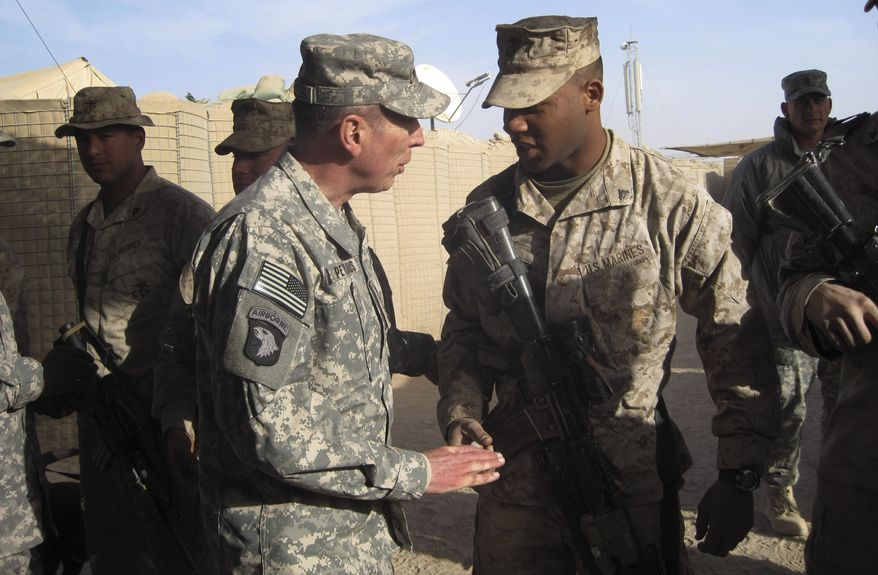 Gen. David H. Petraeus (left), top U.S. and NATO commander in Afghanistan, greets U.S. Marines during a visit to Marjah, Afghanistan, on Saturday, Dec. 25, 2010. Gen. Petraeus crisscrossed Afghanistan on Saturday to visit coalition troops on Christmas at some of the main battle fronts in a show of appreciation and support in the 10th year of the war against the Taliban. (AP Photo/Elena Becatoros)
