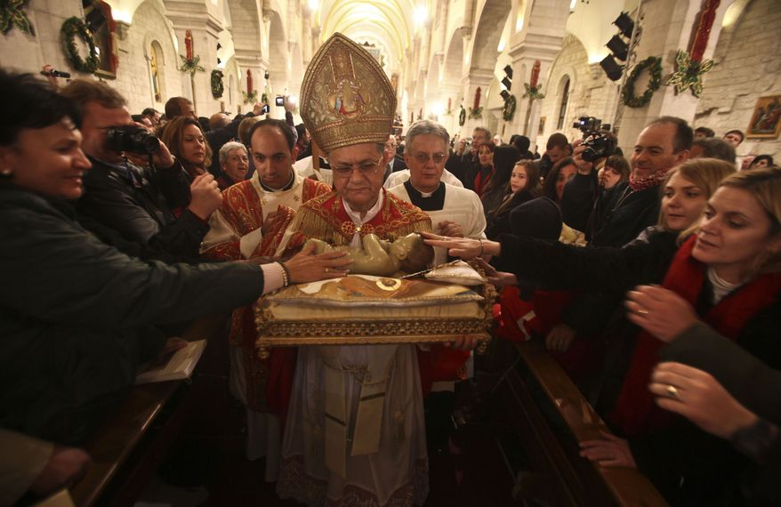 Latin Patriarch of Jerusalem Fouad Twal carries a statuette of the baby Jesus during the midnight Mass marking the beginning of Christmas Day at the Church of the Nativity in the West Bank town of Bethlehem on Saturday, Dec. 25, 2010. (AP Photo/Fadi Arouri, Pool)