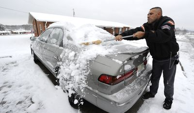 Ramiz Mustafa sweeps several inches of snow from his car on Saturday, Dec. 25, 2010, outside his home in Bowling Green, Ky. Parts of south-central Kentucky received 3 to 4 inches of snow. (AP Photo/Daily News, Joe Imel)