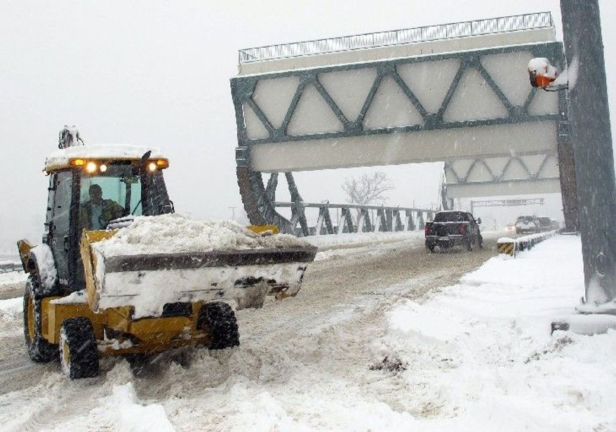 A worker uses a backhoe to clear snow from the center of the drawbridge in Great Bridge Sunday afternoon, Dec. 26, 2010 in Chesapeake, Va. (AP Photo/The Virginian-Pilot, Randall Greenwell)