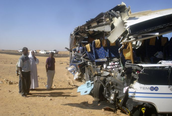 Egyptian men observe the wreckage of a tour bus that crashed into a truck near Aswan, Egypt, on Sunday, Dec. 26, 2010, as it was making the 115-mile journey from Aswan to the ancient temples of Abu Simbel. The crash killed eight American tourists and injured 21, the state news agency said. (AP Photo)